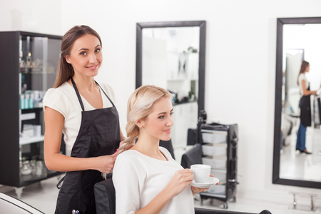 Cheerful young hairstylist is braiding female hair. She is standing and looking at camera happily. The woman is sitting and drinking coffee. Thy are smiling