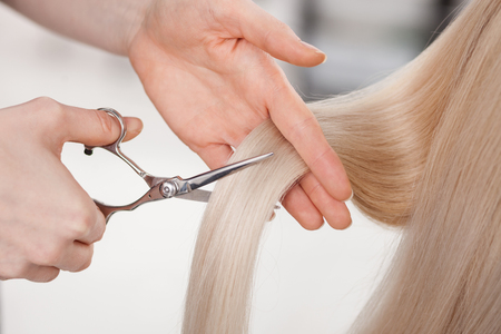 haircut: Close up of hand of hairdresser making haircut for blond woman. She is holding scissors