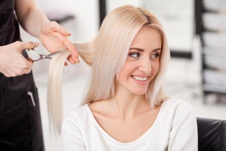 peluquería: Cerca de las manos del peluquero hábil corte de cabello femenina con tijeras. La mujer rubia está sonriendo y mirando a un lado con alegría. Ella está sentada en el salón de peluquería