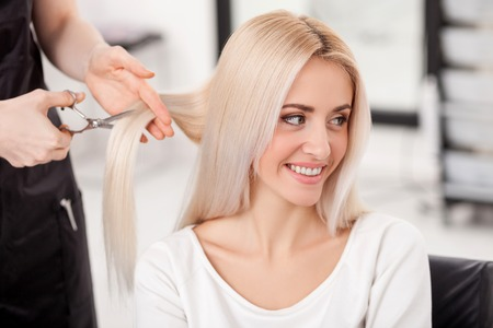 Close up of hands of skillful hairstylist cutting female hair with scissors. The blond woman is smiling and looking aside with joy. She is sitting at hairdressing salon Standard-Bild