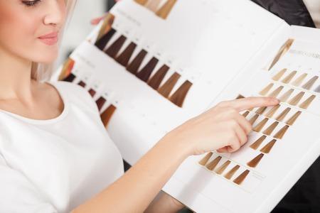 peluquería: Cierre de la mujer joven alegre que se sienta en el salón de peluquería. Ella está sentada y apuntando con el dedo a palet de color de pelo. La señora está sonriendo