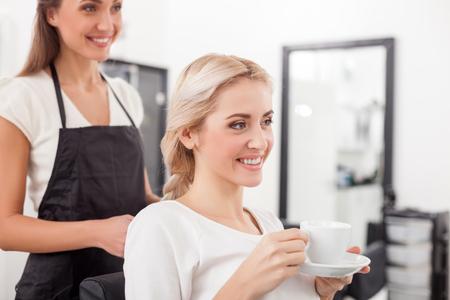 mandil: peluquería joven alegre es el trenzado cabello en la mujer. Ella está de pie en el delantal en el salón de belleza. La mujer está sentada y beber té. Se trata de sonreír felizmente Foto de archivo