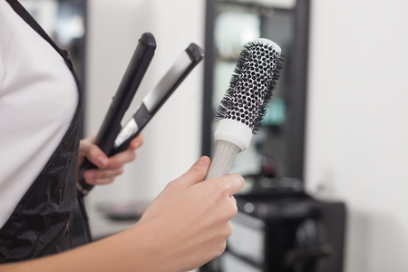 fluting: Close up of hands of professional hairdresser holding a comp and fluting iron. The woman is standing at hairdressing saloon Stock Photo