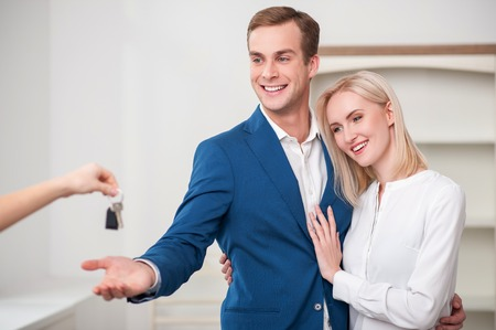 Cheerful loving couple is buying a house. They are embracing and smiling. The realtor is giving a key to the man Stock Photo