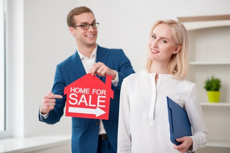 nameboard: Professional realtor is selling a home. The man is holding nameboard and pointing finger at it. The woman is standing and holding documents. They are smiling