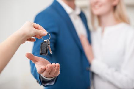 casados: Cierre plano de la mano del agente de bienes ra�ces dando una clave de apartamento para pareja casada. El hombre y la mujer est�n de pie y abrazando. Ellos est�n sonriendo. Centrarse en clave