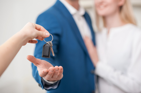married: Close up of hand of realtor giving a key of apartment to married couple. The man and woman are standing and embracing. They are smiling. Focus on key Stock Photo