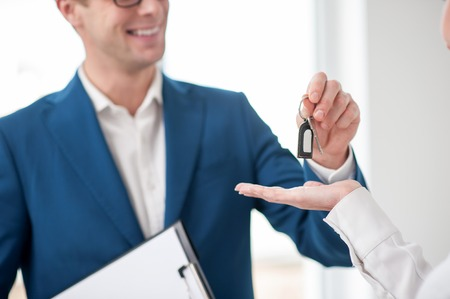 buyer: Close up of successful estate agent selling a house. He is standing and giving a key to the woman. The man is smiling Stock Photo
