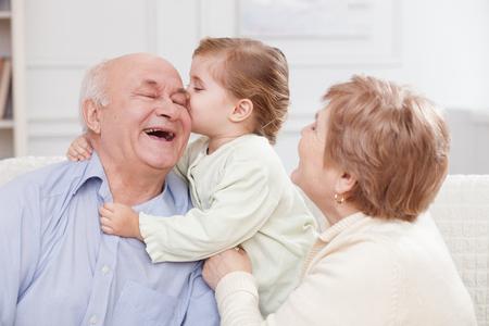 かなり古い男性と女性は、自分の孫娘との時間を費やしています。少女は喜びで彼女の祖父にキスします。彼らはソファの上に座って、笑って 写真素材