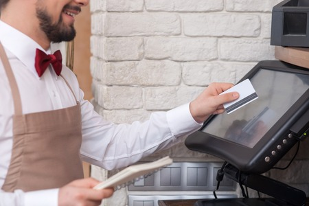 Close up of skillful male cafe worker is swiping credit card through the screen. He is holding a checkbook and smiling Archivio Fotografico