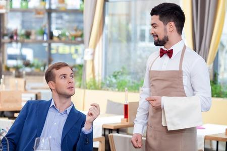 meseros: Atractiva joven camarero está recibiendo una orden. Él está de pie y sonriente. El empresario está sentado en la mesa y hablar. La mujer está mirando el camarero con alegría Foto de archivo