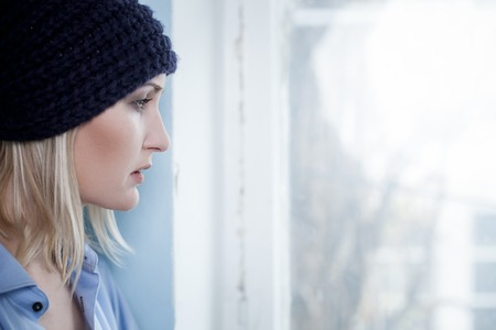 druggie: Depressed female druggie wants a new done. The woman is standing and looking through the window with disappointment. Copy space in right side Stock Photo