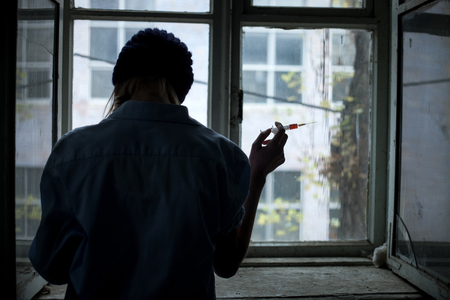 druggie: Frustrated young druggie is holding a syringe of heroine and preparing for injection. The woman is standing near the window. Focus on her back