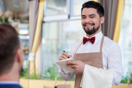 noting: Skillful young waiter is serving a customer and smiling. He is standing and noting an order. The man is looking at the businessman with joy Stock Photo