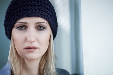 Lonely young woman is standing and crying. The drug addict is looking at camera with frustration. Copy space in right side