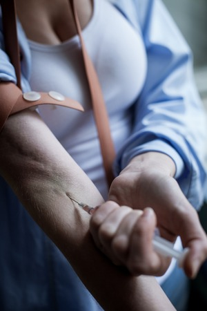 work addicted: Close up of hands of young druggie injecting narcotic into her arm. The woman is standing and holding a syringe Stock Photo