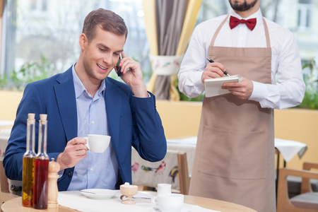 noting: Attractive businessman is drinking coffee in restaurant. He is sitting at the table and talking on the phone. He is smiling. The waiter is standing and noting an order