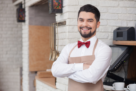 side order: Attractive male cafe worker is standing near checkout machine. He is looking forward and smiling. The man is preparing an order. Copy space in left side