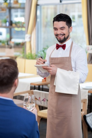 noting: Attractive male cafe worker is receiving an order. He is standing and smiling. The man is writing down notes. The businessman is sitting at the table Stock Photo