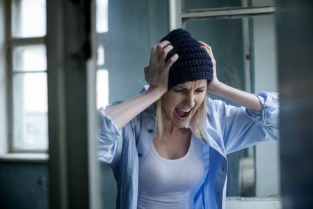 drogadiccion: Frustrados drogadicto rubia está gritando con la depresión. La mujer está de pie y tocar su cabeza con dolor