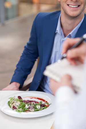 noting: Close up of hands of waiter noting an order of the customer. The businessman is sitting at the table and smiling