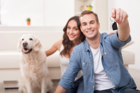 Pretty young husband and wife are preparing for move in new house. They are sitting on flooring and smiling. The man is holding a key. The woman is stroking a dog