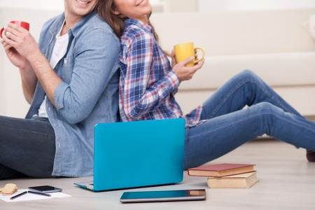 Close up of young husband and wife drinking coffee at home. They are sitting on floor and watching a notebook. The man and woman are smiling