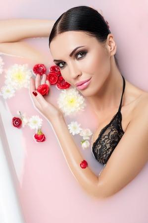 mujer con rosas: Bella joven está tomando un baño con flores. Ella está mintiendo y sonriendo. La señora está en contacto con la rosa y mirando a la cámara con pasión