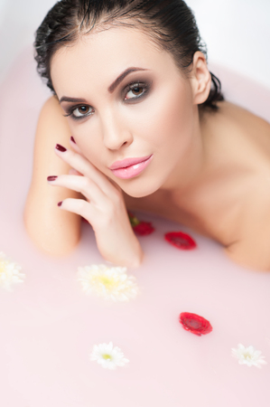 nude woman sitting: Cheerful woman is relieving stress in warm water with flowers. She is sitting in both and looking at camera with desire Stock Photo