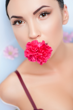 woman in bath: Beautiful healthy girl is taking a bath with enjoyment. She is holding a flower in her mouth. The lady is lying and looking forward with passion Stock Photo
