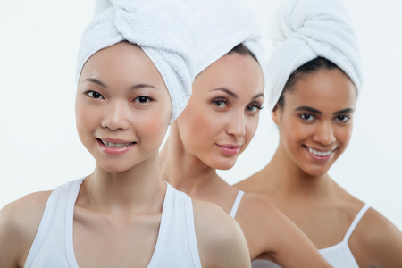 caucasian appearance: Cheerful three girls are standing with white towels on their hair. They have asian, African and Caucasian appearance. The ladies are smiling Stock Photo