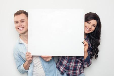 simbolo uomo donna: Bella giovane coppia amorosa sta mostrando un cartello vuoto bianco alla fotocamera. Essi si nascondono dietro di esso e sorridente. Isolato