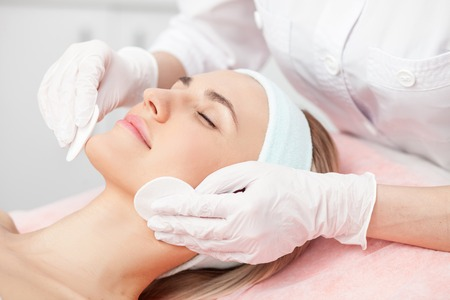 Close up of hands of skillful beautician cleaning and touching female face with sponge. The woman is lying and relaxing. Her eyes are closed with pleasure Stock Photo