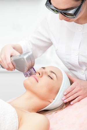 therapy equipment: Cheerful beautician is undergoing laser treatment for female face. She is standing and wearing goggles. The woman is lying and relaxing. She closed her eyes with enjoyment
