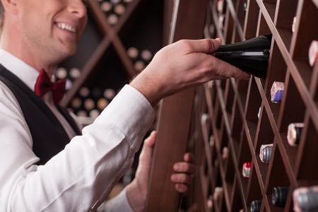 Fröhliche junge Sommelier aus dem Regal eine Flasche Getränk nehmen. Er steht auf der Leiter in Keller. Der Mann lächelt