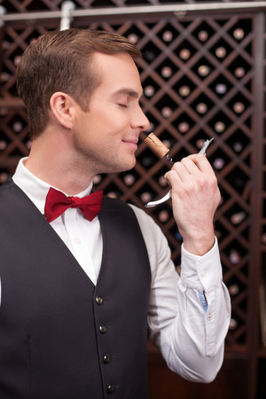 cork: Cheerful young sommelier is smelling a cork of wine. He is holding a corkscrew and smiling. The man is standing in a cellar. His eyes are closed with pleasure
