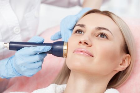 Close-up van de handen van de schoonheidsspecialiste cavitatie behandeling op menselijk gezicht met de apparatuur. De vrouw ligt en zachtjes glimlachend Stockfoto