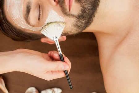 Close up of hand of therapist applying cream on male face. The man is lying at spa. His eyes are closed with enjoyment