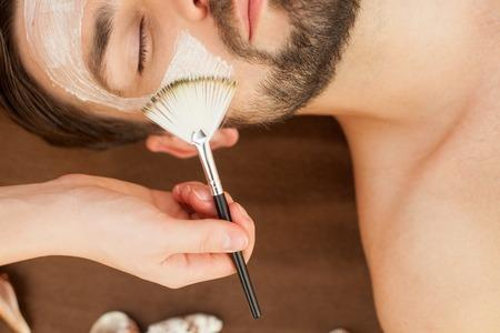 Gros plan de la main du thérapeute d'appliquer la crème sur le visage des hommes. L'homme est couché au spa. Ses yeux sont fermés à la jouissance
