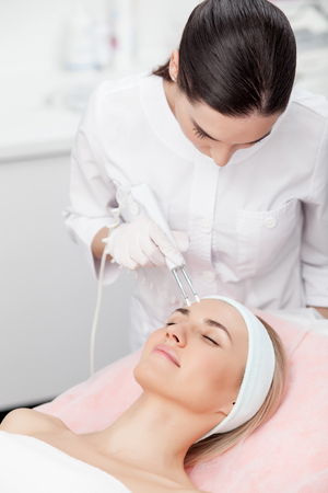 resurfacing: Skillful beautician is undergoing cavitation treatment on human face. She is standing and looking down with concentration. The woman is lying with pleasure