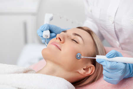 resurfacing: Beautiful young woman is getting cavitation treatment at beauty saloon. She is lying and relaxing. The lady closed her eyes with pleasure. The beautician is touching equipment to female face Stock Photo
