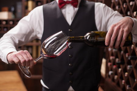sommelier: Close up of hands of young sommelier pouring red wine from bottle into glass. He is standing in a cellar
