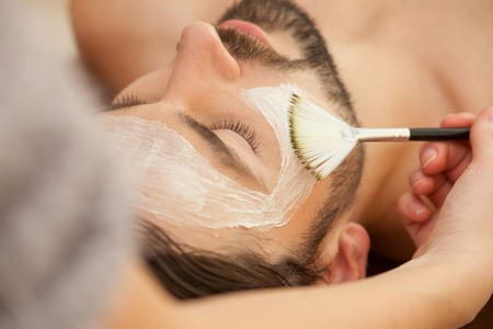 Close up of attractive man lying and relaxing at spa. The beautician is applying facial cream on his skin
