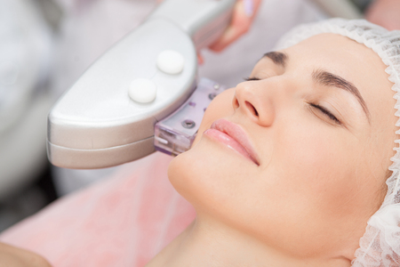 Close up of hand of beautician undergoing photorejuvenation of the skin on human cheek. The woman is lying and smiling
