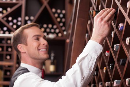 Attraktiver Sommelier nimmt eine Flasche Wein vom Regal. Er steht und lächelt in einem Keller