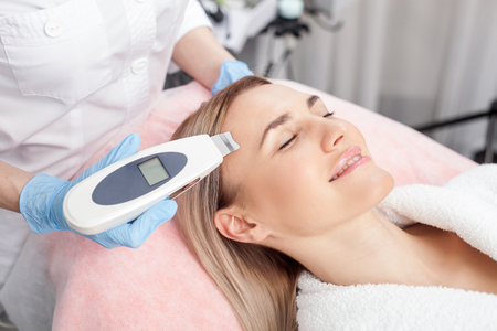resurfacing: Cheerful woman is getting skin treatment at spa. She is lying and smiling. The beautician is treating her skin with the equipment