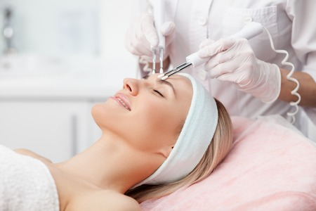 resurfacing: Close up of hands of professional beautician touching female forehead with the equipment. The young woman is lying and smiling