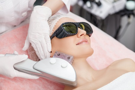 Beautiful young girl is getting laser treatment on her face. She is lying and smiling. The woman is wearing goggles Stock Photo