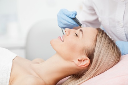 aging: Close up of arms of experienced beautician undergoing laser skin treatment of skin on female face. The young woman is lying and smiling