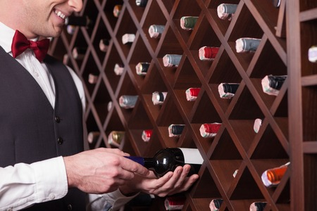 sommelier: Close up of professional sommelier choosing a bottle of wine in a cellar. He is standing and laughing Stock Photo